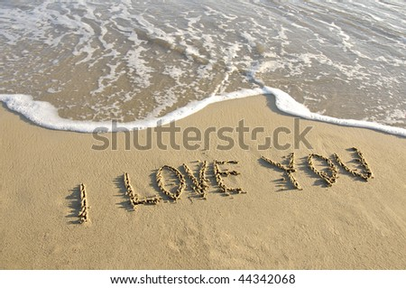 """I Love You"" written on the deserted beach with wave rolling. - stock photo"