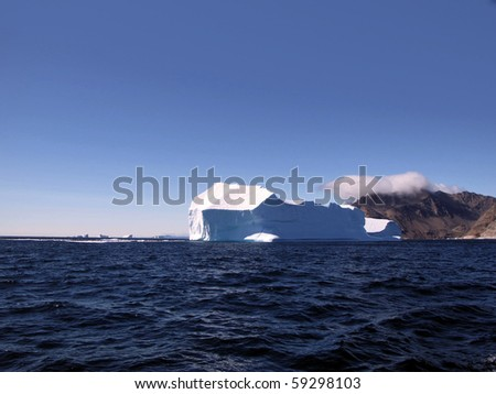 Iceberg in Greenland with land showing in background - stock photo