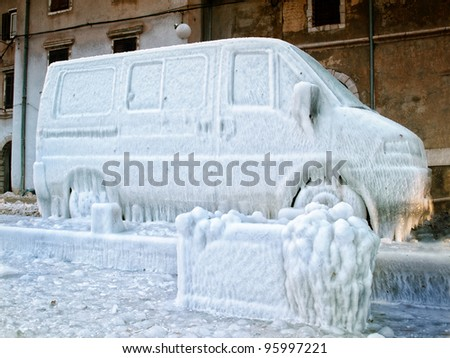 Icebound van due to strong wind, splash of sea  and very low temperatures. - stock photo