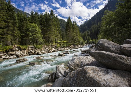 Idyllic landscape. Upper courses of falls - rather narrow fast seething small river among green mountain meadows. National park Krimml in Austria - stock photo