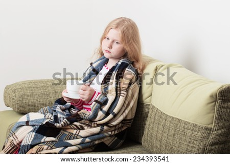 ill girl child with cup of hot tea - stock photo