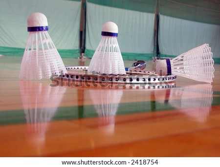 Image of few shuttlecocks and a badminton racket on the floor with interesting reflections. - stock photo