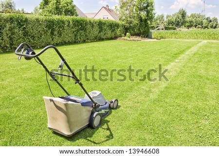 image with a lawn mower ready to cut the grass on a sunny day. - stock photo