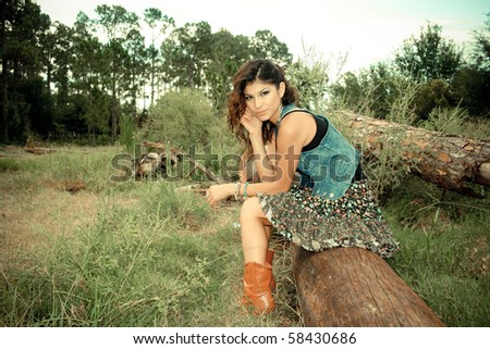 Imaged Are made To Look like old Camera style Picture Of a Cowgirl sitting on A log, (Picture is made With old School intended) Such as Effects added a fringing and  Blur - stock photo