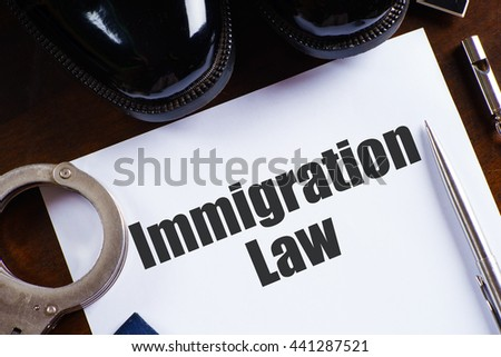 """Immigration law"" text on paper with pen, whistle, handcuff and a pair of black shoes on wooden table - law and enforcement concept - stock photo"