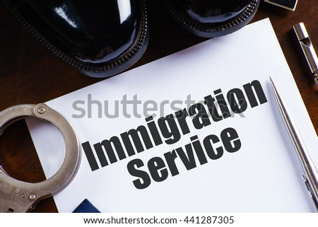 """Immigration service"" text on paper with pen, whistle, handcuff and a pair of black shoes on wooden table - law and enforcement concept - stock photo"