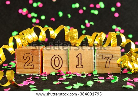 2017 in wooden blocks displayed with pink and green confetti and a gold ribbon on a black background