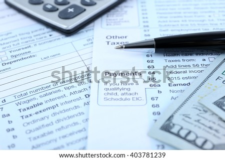 1040 Income Tax Form and dollar bills, close up