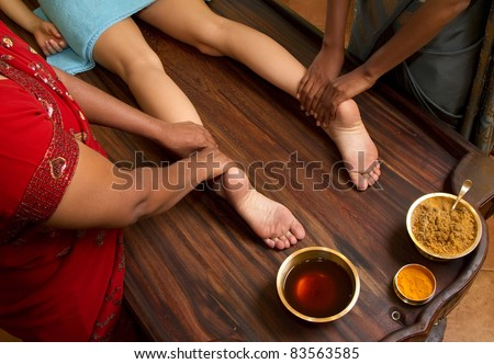 indian doctors doing traditional ayurvedic oil foot massage - stock photo