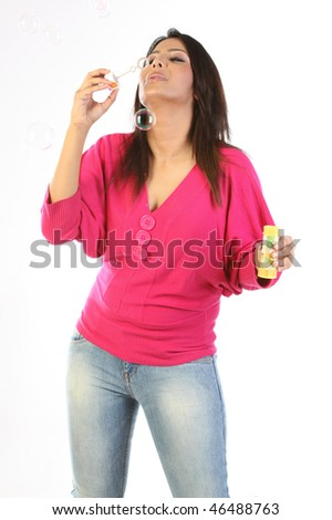Indian modern girl blowing bubbles  with bubble maker - stock photo