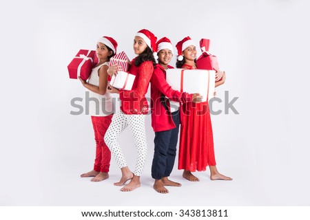 4 indian teenagers holding christmas gifts with santa hat on head, isolated on white background, standing close, indian kids and christmas, asian kids and christmas - stock photo