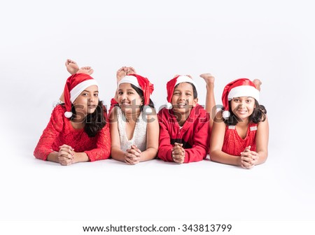 4 indian teenagers with red cloths and red santa hat, lying on white floor for photo, isolated on white background, close, indian kids and christmas, asian kids and christmas, legs folded, front view - stock photo