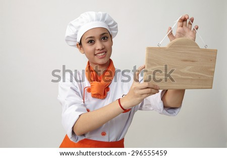 Indian woman with chef uniform holding a woden plank - stock photo
