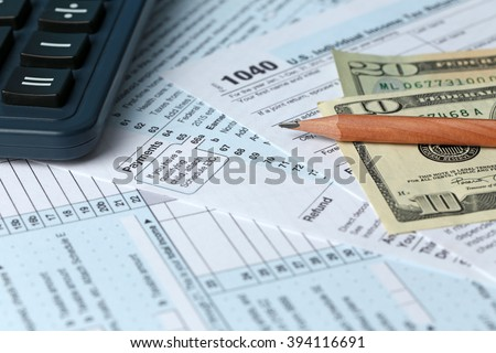1040 Individual Income Tax Return Form for 2015 year with a pencil to fill in, calculator and dollar bills, close up - stock photo