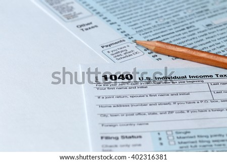 1040 Individual Income Tax Return Form for 2015 year with a pencil to fill on the white desk, close up - stock photo