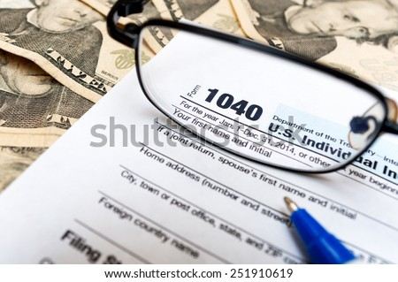 1040 individual tax return form, glasses and dollar bills - stock photo