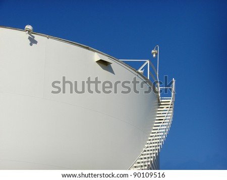 industrial tank with ladder and blue sky - stock photo