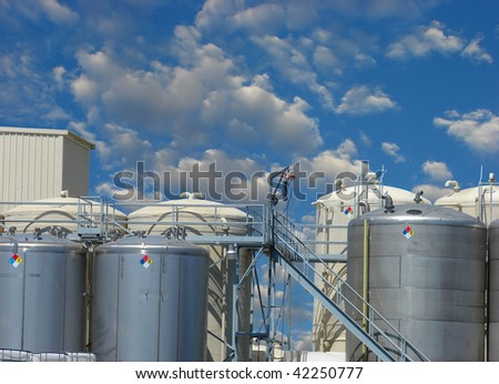 Industrial tanks and silos with cloudy sky - stock photo