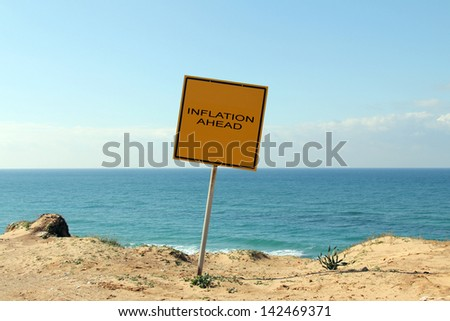 Inflation ahead sign on the edge of a hill overlooking the sea: The sign warns: Danger, Stay Back, Unstable Cliffs,  Keep Out - stock photo