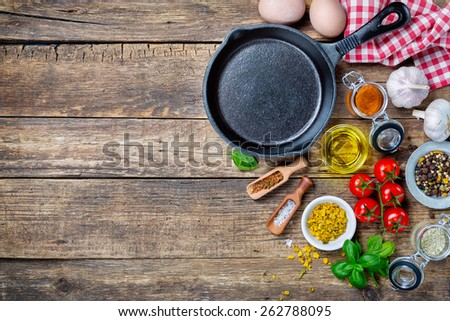 Ingredients for cooking and cast iron skillet on an old wooden table. Food background concept with copyspace - stock photo