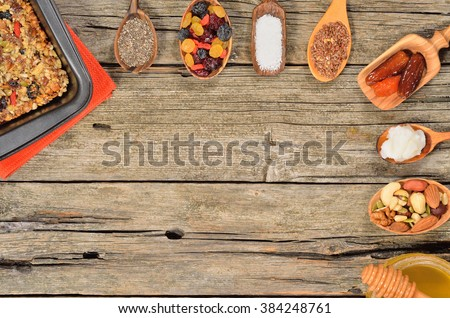 Ingredients for homemade granola bars - dried fruits, nuts, seeds and honey on wooden table. Paleo diet. Copyspace background. Top view. - stock photo