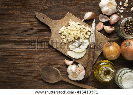 Ingredients with garlic cloves, onion and spices on wooden background.