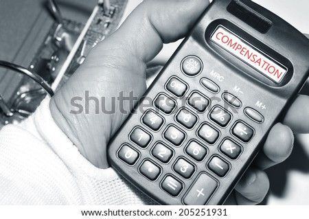 Injury claim concept with injured hand holding calculator - stock photo