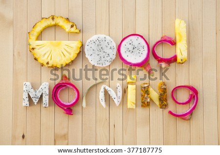 inscription from tropical fruit good morning, letters of sliced fruit, the original lettering of the bright, tasty, juicy and pineapple and Dragon fruit on wooden boards, closeup, lay flat - stock photo