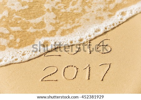 2016 2017  inscription written in the wet yellow beach sand being washed with sea water wave. Concept of celebrating the New Year at some exotic place - stock photo