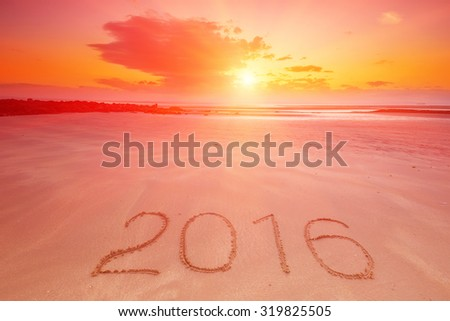2016 inscription written in the wet yellow beach sand. Concept of celebrating the New Year. - stock photo