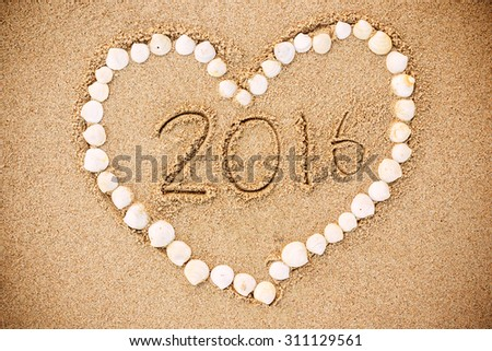 2016 inscription written in the wet yellow beach sand with Heart-shaped shell. Concept of celebrating the New Year  - stock photo