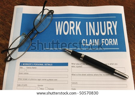 insurance: blank work injury claim form on desk - stock photo