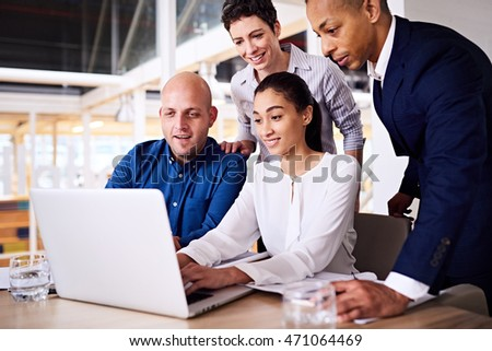 4 intelligent business partners all looking at the same notebook screen at their latest promotional video that was just sent through by the creative department.