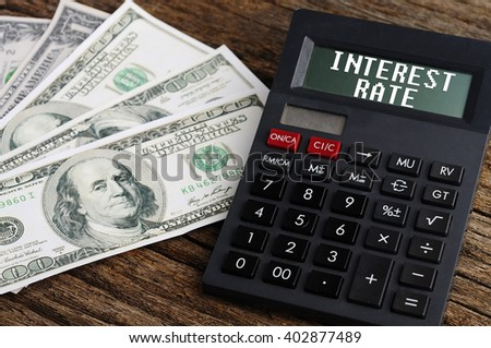 """""""INTEREST RATE"""" Word On Calculator with Dollars On Wooden Background - stock photo"""