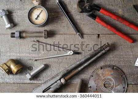 internal screws, pencil, bolts, manometer, diamond wheel, tools on old wooden table ,  - stock photo