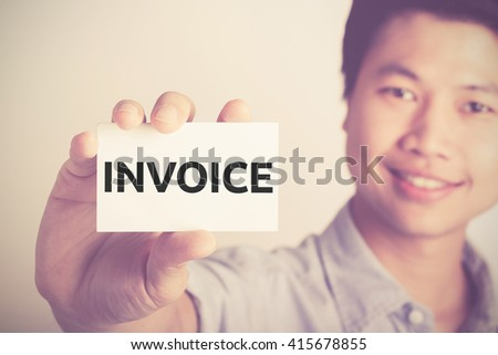 """"""" Invoice """" word on card hold by smiling man - stock photo"""