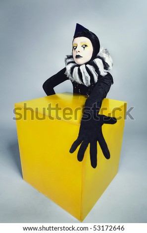 ?ircus fashion mime posing near a yellow square on a grey background. Photo. - stock photo