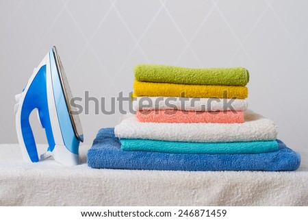 ironing tool and towels on white background - stock photo
