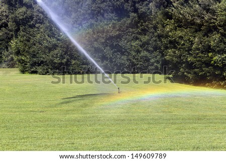 irrigation water splash green garden rainbow colors - stock photo