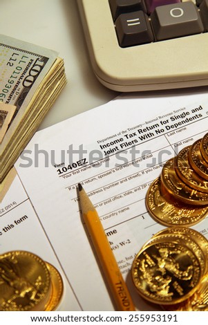 1040 irs tax return with pencil eraser and gold and money calculator - stock photo
