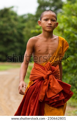 4000 ISLANDS, LAOS - SEPTEMBER 22:  Monk walking in direction of the temple in 4000 Islands, Laos on September 22, 2011. Buddhist monk from Laos in traditional orange costume. - stock photo