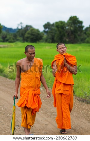 4000 ISLANDS, LAOS - SEPTEMBER 22:  Monks walking in direction of the temple in 4000 Islands, Laos on September 22, 2011. Buddhist monks from Laos in traditional orange costume. - stock photo