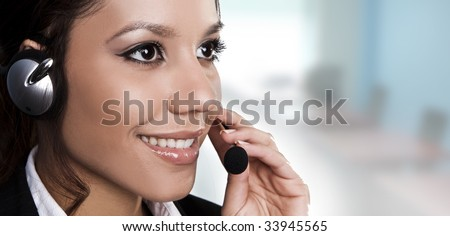 Isolated portrait of a beautiful help desk or support line operator answering a call. - stock photo