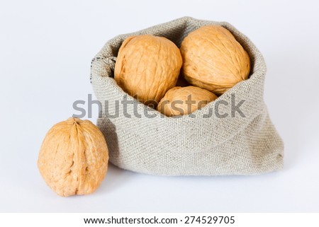 Isolated walnuts in the linen bag on a white background
