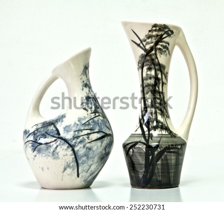 Israeli ceramic pair  Black white blue tones  Two vases of 1950-th years. Unusual forms Glazed surfaces  Floral drawing  Symbolizes couple: He - She  Brother - sister  Bride - groom etc. On white. - stock photo