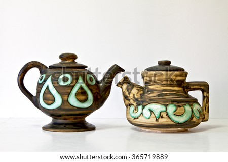 Israeli ceramic pair of 1950-th years. Dark brown and green tones, inlay, glazed blotches, stylized floral ornament. Symbolizes couple: He - She brother- sister bride -groom etc. Isolated on white. - stock photo