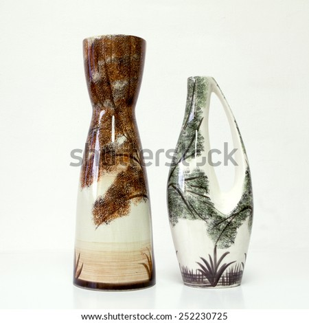 Israeli ceramic pair  White brown green tones  Two vases of 1950-th years. Unusual forms  Glazed surfaces  Floral drawing  Symbolizes couple: He - She  Brother - sister Bride - groom etc. On white. - stock photo