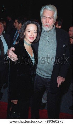 """28JAN99:  Actor JAMES COBURN & girlfriend PAULA MURAD at the world premiere, in Los Angeles, of his new movie """"Payback"""" in which he stars with Mel Gibson & Maria Bello.  Paul Smith / Featureflash - stock photo"""