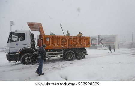 09 January 2016, Istanbul, Turkey. workers aspersing salt on ground to prevent icy ground as people walk under snowstorm.