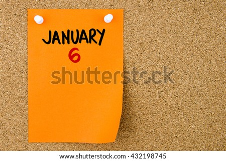 6 JANUARY written on orange paper note pinned on cork board with white thumbtacks, copy space available - stock photo